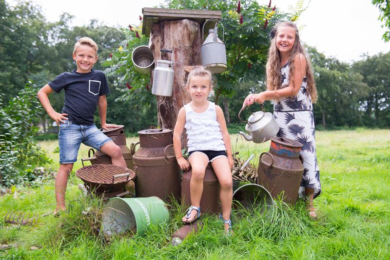 kinderen bij oude melkbussen